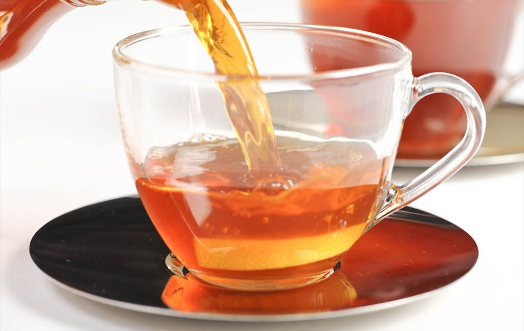 a clear cup of rooibos tea with teapot in the background.