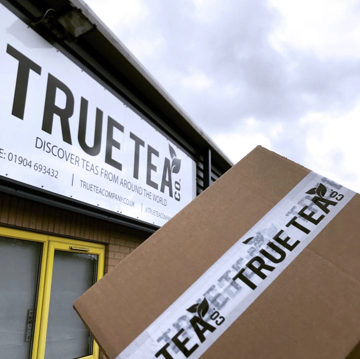 holding a true tea box above our office sign in york